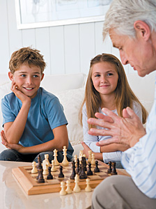 senior and kids playing chess - Copyright – Stock Photo / Register Mark